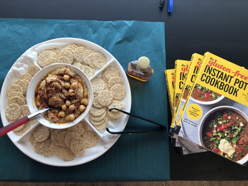 Instant Pot Hummus with crackers and a stack of Gluten Free Instant Pot Cookbooks